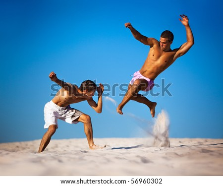 Two young men sport fighting on beach. - stock photo
