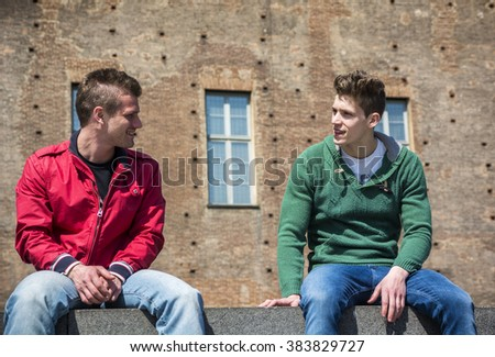 Two young men talking while sitting on curb - stock photo