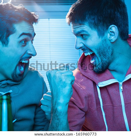Two young men watching sports competition and drinking beer. - stock photo