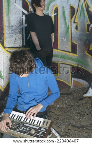 Two young men with music equipment next to graffitied wall - stock photo