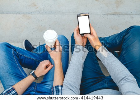 Two young men with the phone in his hand sitting on the steps. top view - stock photo