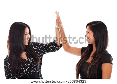 Two young mixed race business woman giving high five for success isolated on white background - stock photo