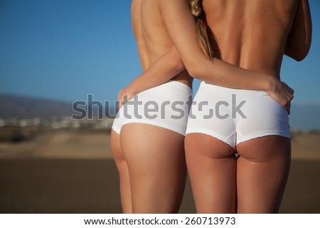 two young model in the beach with white swimsuit - stock photo