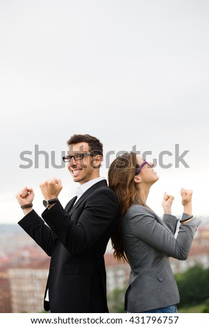 Two young modern entrepreneur partners celebrating business success. Man and woman gesturing outside. - stock photo