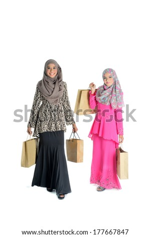 two young Muslim woman in head scarf with modern clothes with shopping bags, isolated on white - stock photo