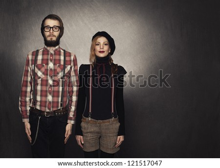 two young nerds standing and looking at camera on grunge background - stock photo