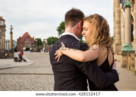 two young people - a man in black suit and a woman wearing black dress - dancing tango outside; people are walking and enjoying warm evening, a musician is playing romantic songs - stock photo