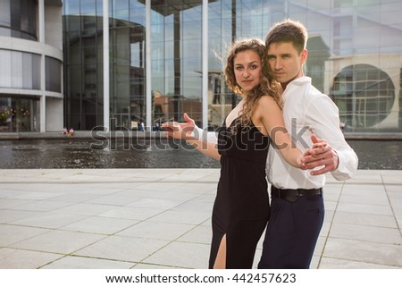 two young people - a man in white shirt and a woman wearing black dress - dancing tango outside on city embankment - stock photo