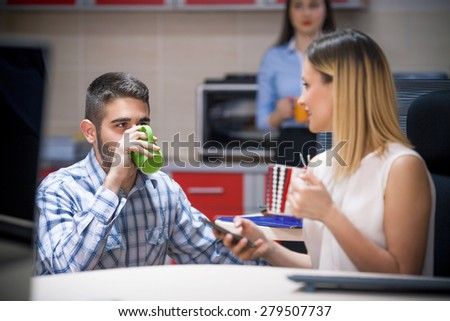 Two young people drinking coffee in an office - stock photo