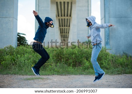 Two young people in the respirators jumping outdoors - stock photo