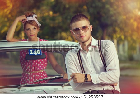 Two young people posing in front of their car - stock photo