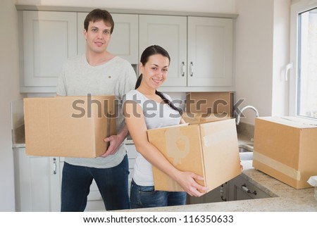 Two young people relocating in kitchen - stock photo