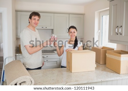 Two young people standing in the kitchen and while celebrating the relocation - stock photo