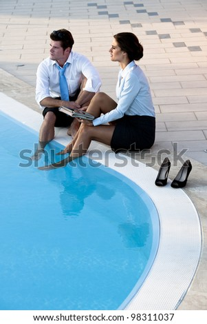 Two young people working free with feet in the pool - stock photo