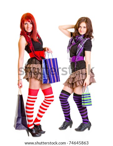 Two young pleased girlfriends standing with shopping bags in hands isolated on white - stock photo