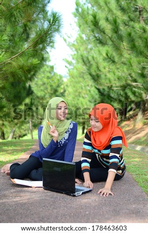 Two young pretty Asian muslim college girl with book and laptop - stock photo