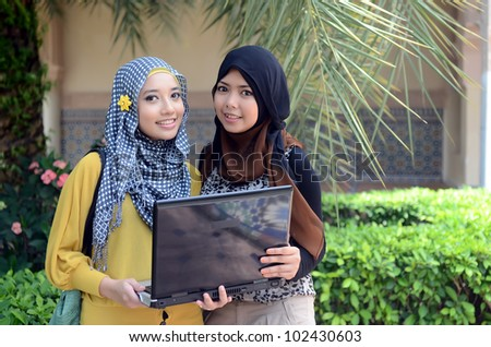 Two young pretty Asian muslim college girl with laptop and smile - stock photo