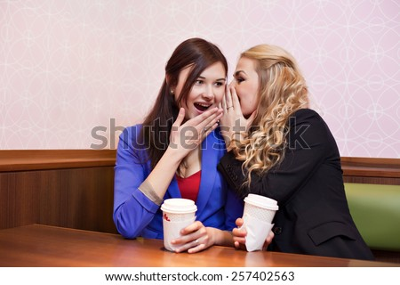 Two young pretty caucasian girls with long hair drinking coffee, chatting and having fun at a cafe - stock photo