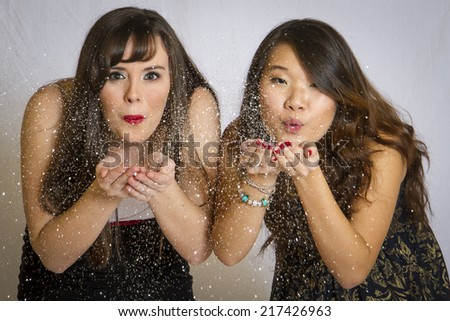 Two young pretty girls blowing glitter from their hands. - stock photo