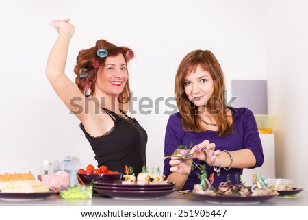 Two young pretty woman housewife cooking with curlers on hair - stock photo