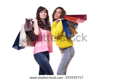 two young pretty woman standing isolated on white background paper shopping bags from the store. - stock photo