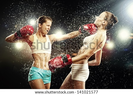 Two young pretty women boxing standing against flashes background - stock photo