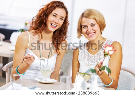 Two young pretty women sitting at cafe and eating dessert - stock photo
