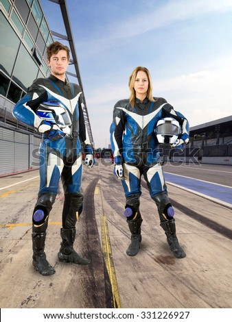 Two young riders, a man and a woman, from the same motorsports team posing in the pits lane of a race track  - stock photo