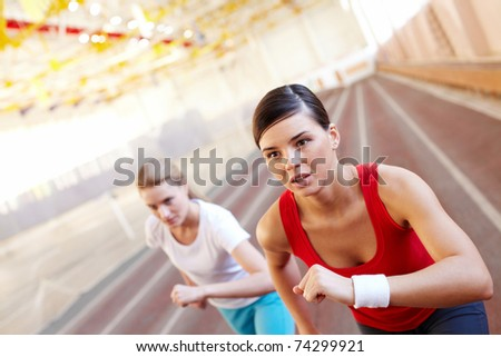 Two young runners competing in gym - stock photo