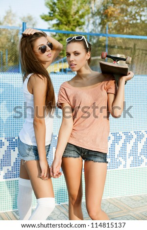 Two young sensual friends in park, outdoors - stock photo