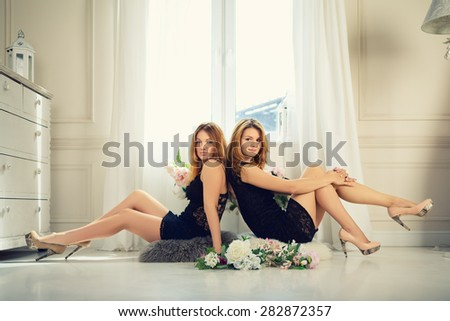 two young sexy girls sitting on a floor in front of window - stock photo
