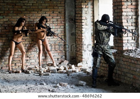 Two young sexy women with rifles and soldier - stock photo