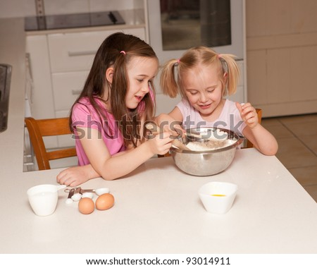 Two young sisters baking cupcakes in their kitchen at home in their domestic kitchen. - stock photo