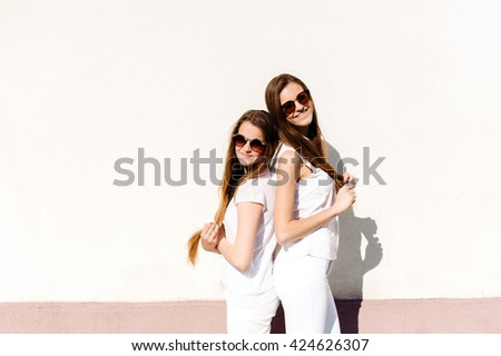 Two young sisters in a good mood walking through the city streets. They are happy to be together. They are dressed in trendy modern clothing. The girls have a beautiful long hair - stock photo