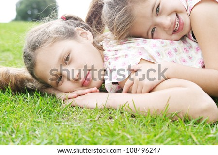Two young sisters laying down on green grass in the park, laughing and smiling, having fun playing. - stock photo