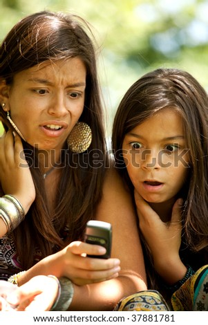 two young sisters reading a new sms at the cellular - stock photo