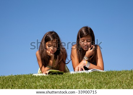 two young sisters reading books at the park - stock photo