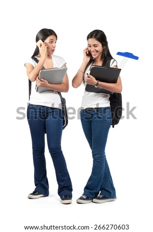Two young smiling girls talking on the phone isolated - stock photo