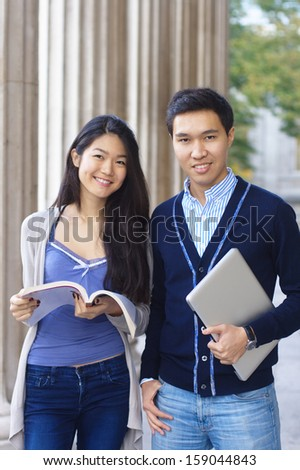 Two young smiling university students on campus  - stock photo
