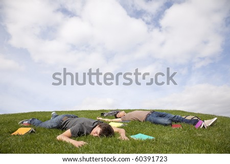 two young student lying down at the school grass after long hours of study - stock photo