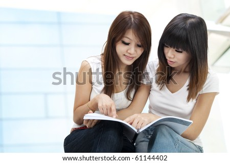 Two young student sitting outside school building - stock photo