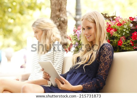 Two young students with digital tablet sitting at cafe and making presentation. - stock photo