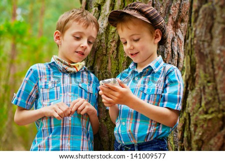 Two young stylish boys browse the internet on mobile phone - stock photo
