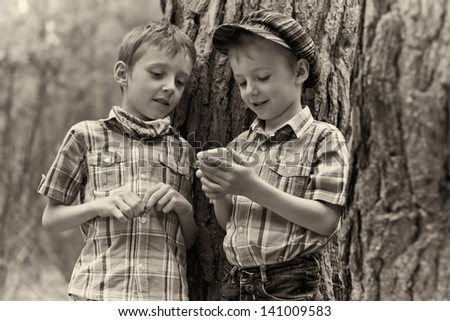 Two young stylish boys browse the internet on mobile phone. Vintage postcard. - stock photo