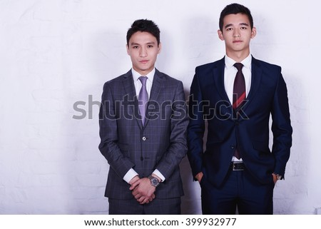 Two young successful Asian businessmen dressed in suits are posing for camera during work break, while are standing in office interior against wall with copy space for your advertising text message - stock photo