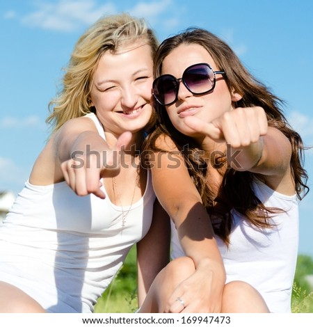 Two young teenage girls giving thumbs up at blue sky background - stock photo