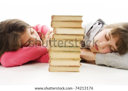 Two young teenage girls with pile colored book fell asleep after hard learning. - stock photo