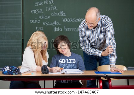 Two young teenage students, a girl and boy, sitting at a desk with their class notes being helped by a balding male teacher - stock photo