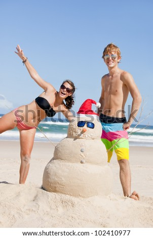 Two young teens having fun with Snowman made out of sand on beach during christmas. Escaping the cold travel concept.  - stock photo