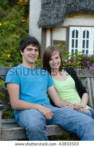 Two young teens smiling and sitting on a park bench outside - stock photo